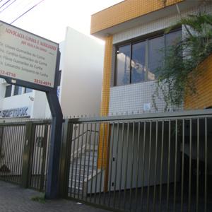 No canteiro da parte superior do sobrado, as plantas se debruçam sobre a frente azulejada do escritório de Uberlândia/MG.