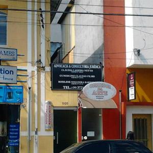Em rua movimentada na Cidade das Fontes, Poços de Caldas/MG, a placa do escritório se destaca em meio a outras placas.
