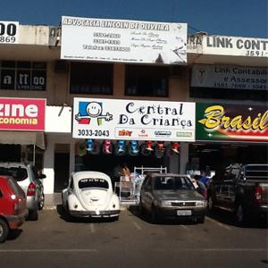 A placa do escritório se mistura com os letreiros dos pontos comerciais da cidade satélite Sobradinho/DF.
