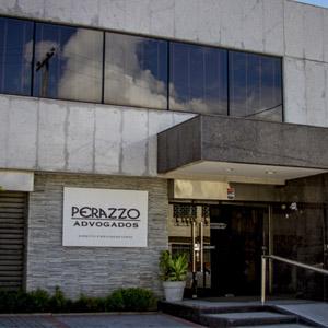 A placa com o nome do escritório de Recife/PE chama atenção na parede trabalhada com sobreposição de pedras.
