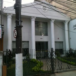 De dentro do bonde, na rua Brás Cubas, avista-se a fachada do grande escritório localizado no centro histórico de Santos/SP.