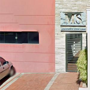 Na placa de alumínio, o nome do escritório de Botucatu/SP em letras vazadas se destaca na parede de pedras.