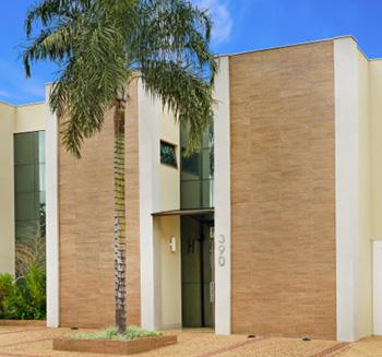 No escritório em Ribeirão Preto/SP, os tons claros da fachada trazem suavidade e harmonia com o jardim bem cuidado.