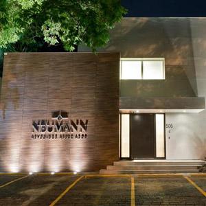 Os tons amadeirados e a vegetação no entorno da residência marcam a fachada da banca de SP.