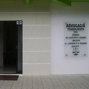 Na parede de cor neutra do escritório de Vilhena/RO, a placa de vidro evidencia a fachada da banca.