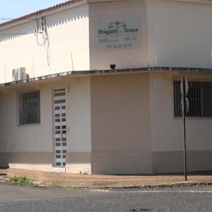 A luz do sol ilumina a frente da fachada de Araguari/MG, evidenciando a cor neutra do escritório.