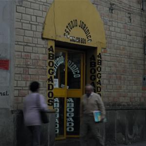 Em Tarija/Bolívia, a fachada amarela do escritório sobressai na parede de tijolos à vista.