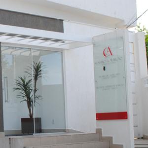 O vermelho do logotipo do escritório de Goiânia/GO se destaca na parede de tom neutro e sério.