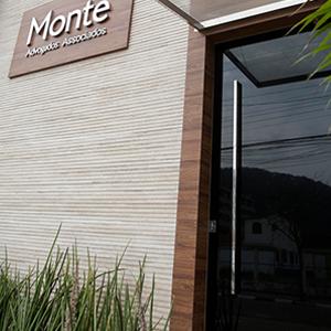 A placa de madeira com o nome do escritório do Guarujá/SP sobressai na parece texturizada.