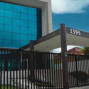 No suntuoso prédio espelhado se encontra o escritório de Recife/PE, protegido por uma extensa grade preta e câmera de segurança.