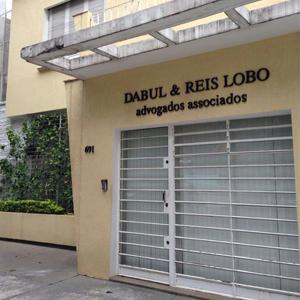 As letras pretas se destacam na parede com textura grafiato do escritório de São Paulo/SP.