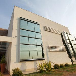 O bom tempo emoldura o cenário brasiliense. Na capital Federal, o escritório apresenta em sua estrutura grandes janelas espelhadas que refletem os pinheiros do verde jardim e elementos urbanos como os postes de luz.