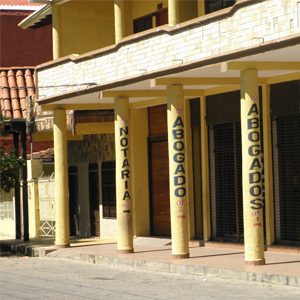 As setas desenhadas nos pilares da construção de cor amarela, em Santa Cruz de la Sierra/Bolívia, indicam mais à frente um escritório de advocacia.