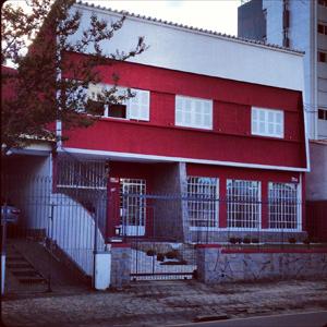 Na antiga casa situada no tradicional bairro Alto da rua XV, em Curitiba/PR, o escritório mescla em sua fachada o tom vermelho com detalhes em pedra.