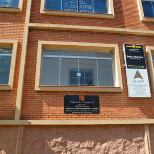 A placa do escritório de Poços de Caldas/MG sobressai na fachada do prédio de tijolos à vista.