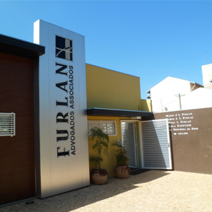 A placa metalizada com o nome do escritório de Marília/SP se destaca entre as paredes coloridas.