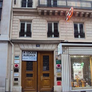 As placas ao lado da porta de madeira maciça indicam inúmeras salas ocupadas no prédio parisiense. Do lado direito, a sexta placa corresponde a uma banca advocatícia, da cidade luz, Paris.