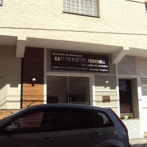 No painel de madeira, a letras prateadas que formam o nome do escritório de Caxambu/MG são realçadas pela luz do sol.